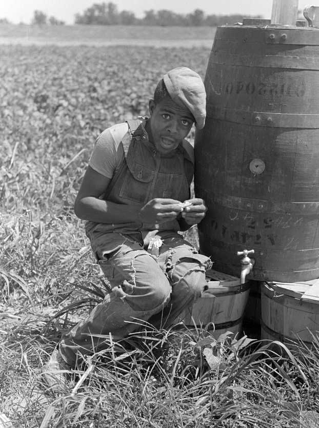 Young African American day laborer rolling a cigarette in a field near Muskogee, Oklahoma Photo: Russell Lee