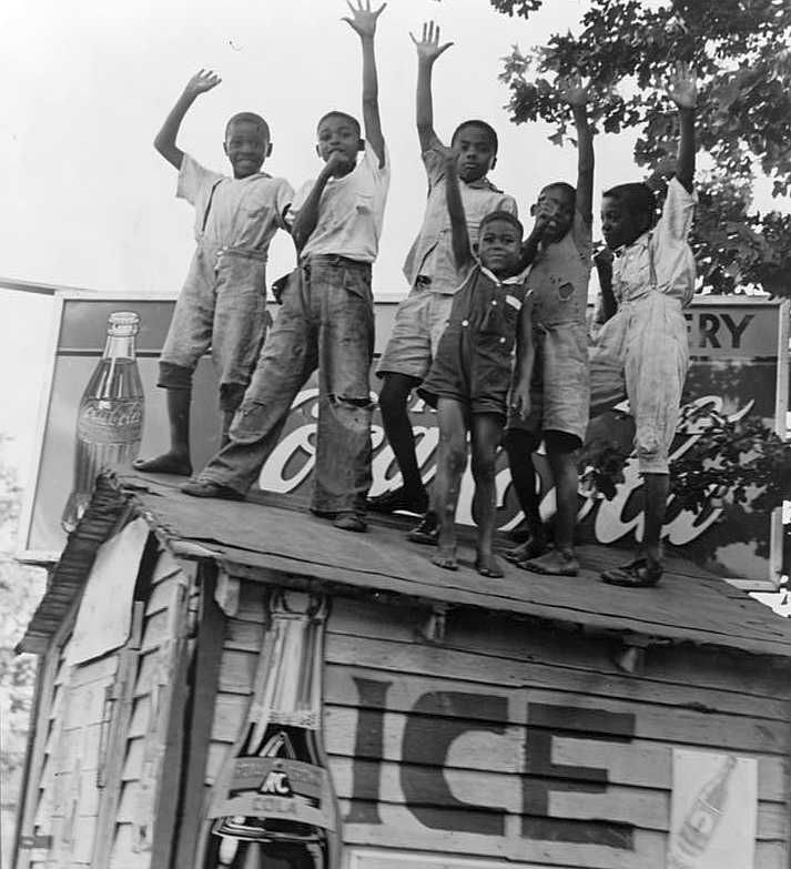 Children playing on top of Coca Cola stand, Little Rock, Arkansas  Photo: Dorothea Lange