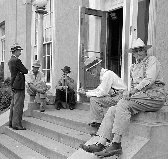Men sitting on steps of post office, Lafayette, Louisiana    Photo: Russell Lee