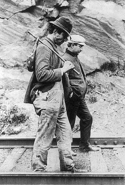 Two hobos walking along railroad tracks, after being put off a train