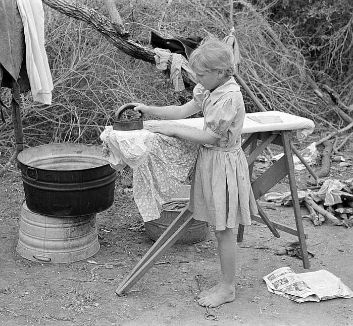 Child of migrant worker ironing in camp near Harlingen, Texas Photo: Russell Lee