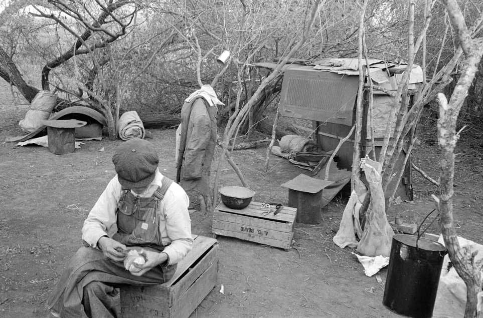 Migrant worker living in camp with two other migrant men. His sleeping quarters and all worldly possession are to be seen in background. Harlingen, Texas Photo: Russell Lee