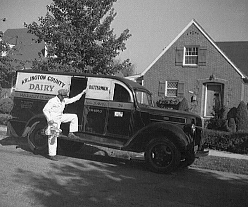 Arlington County, Virginia, dairy truck from which a driver is alighting with a tray of milk bottles  Photo: Howard Liberman