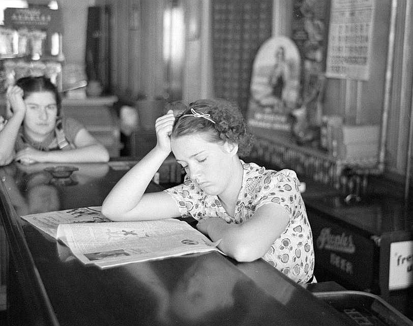 Girl reading newspaper in restaurant, Tower, Minnesota Photo: Lee Russell