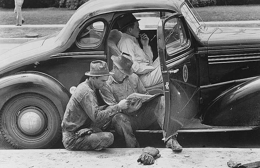 Oil field workers taking timeout to read the paper, oil well, Kilgore, Texas  Photo: Russell Lee