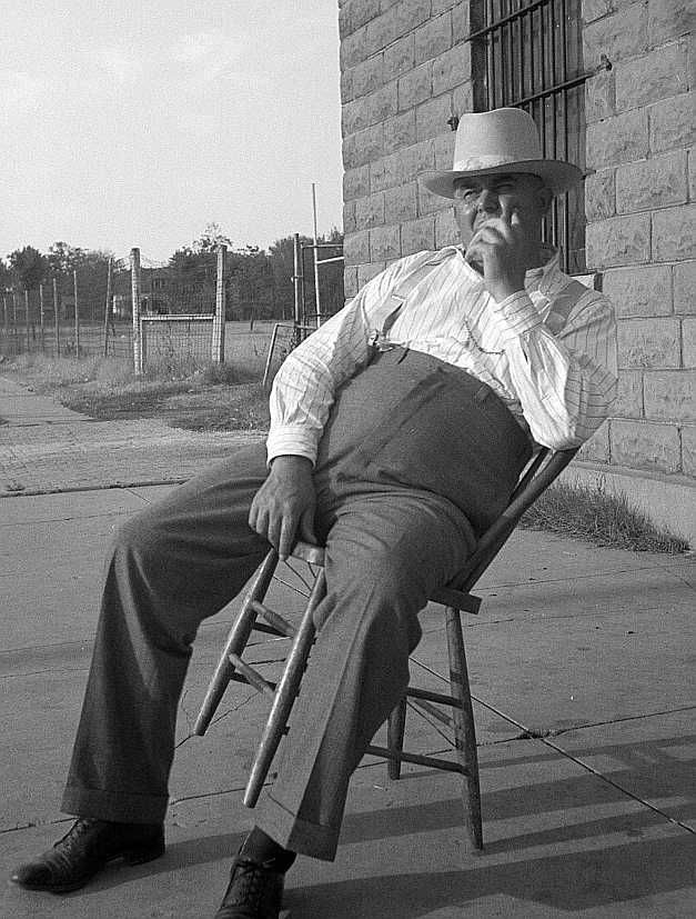 The sheriff of McAlester, Oklahoma, sitting in front of the jail. -- He has been sheriff for thirty years   Photo: Dorothea Lange
